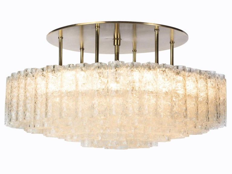 (XL-size) Gorgeous, 1950s Mid-Century Modernist flush mount chandeliers was designed by Doria Leuchten, Germany. It features multi-tiered layers of textured ice glass tubes connected to a circular brushed brass frame. The flush mount with almost 200