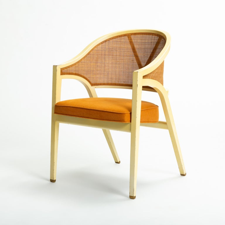 A 1954 design for an elegant armchair by Edward Wormley for Dunbar Furniture. Known as the Y-Back Captain chair for the distinctive forked brace supporting its caned backrest, the design boasts unique strength belied by its graceful frame. Curved