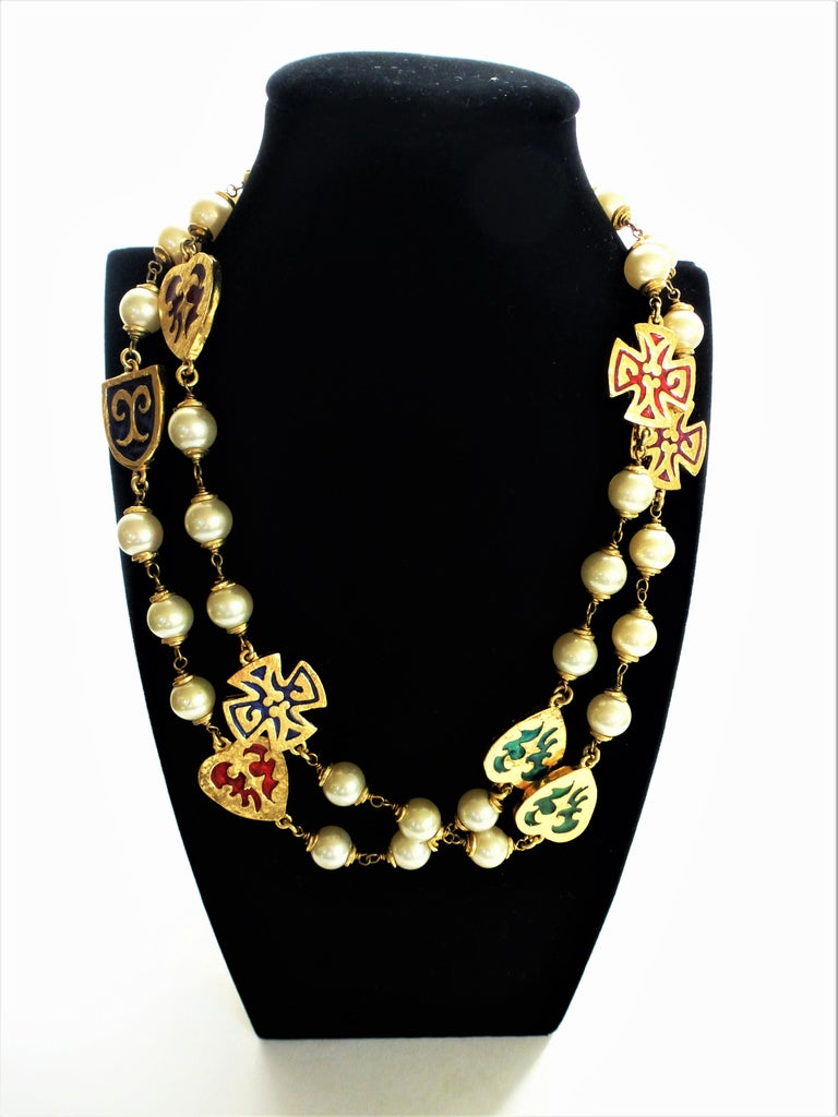 A typical YVES SAINT LAURENT chain with false pearls, in between gold hearts, crosses and signs with enamelled motivs. The chain has a very nice clasp with multiple YSL signatures. it can be worn single or double on the neck. Made about 1980s, gold