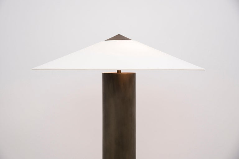 This symmetrical table lamp is comprised of an aged-brass base and a custom linen shade, which is supported by a hand-turned aged-brass CAP that continues the shade's profile. The shade shape is inspired by a mountain and the aged-brass base