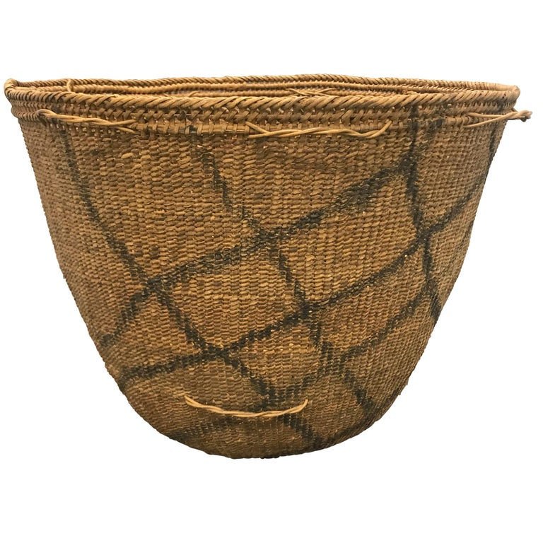 A 20th century Yanomami gathering basket decorated with charcoal line drawings on the exterior. This basket is tightly handwoven of natural fibers with several inner rings for stability, and palm leaf straps. Straps are tied around the small loops