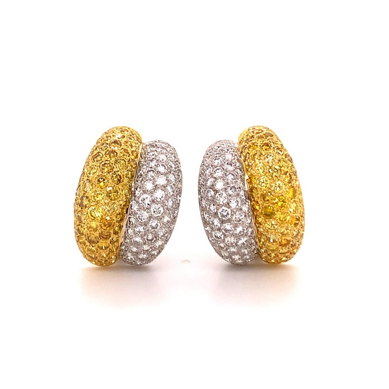 Classic two-row bombé-style, half hoop earclips in 18 karat white and yellow gold.  Pavé set with white and fancy coloured dimonds as follows: - 136 brilliant-cut diamonds of G/H colour and vs clarity, total weight approximately 3.40 carats - 136