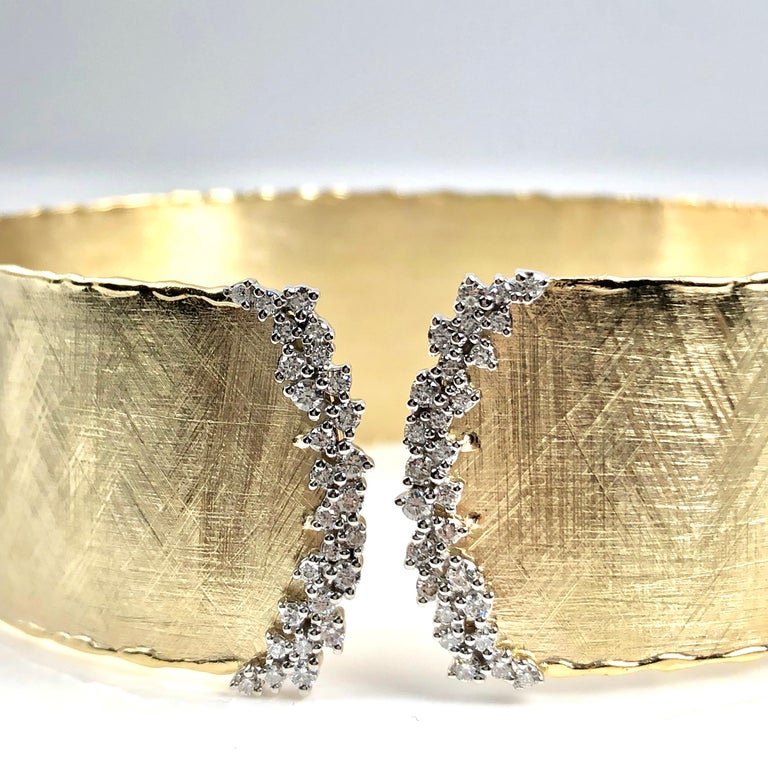 This rustic bangle has a brushed yellow gold design, accented by two rounded curves of round white diamonds at the rounded opening. The bangle is flexible enough to pass over the hand, without any hinge or buckle.  The bangle is set in 14k Yellow