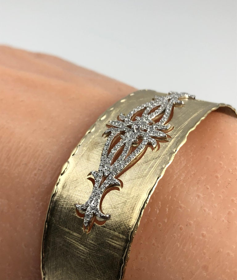 This rustic bangle has a brushed yellow gold design, accented by a diamond- accented cutout opposite the opening. The bangle is flexible enough to pass over the hand, without any hinge or buckle.  The bangle is set in 14k Yellow and White