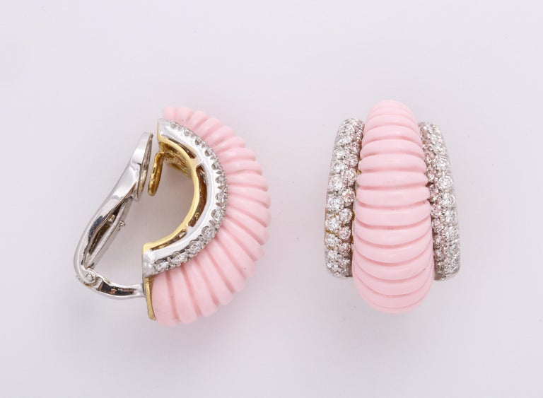 Super chic and sharp 18K yellow gold stylized ''shrimp'' earclips mounted with bombe' (domed) fluted reconstituted pink blush coral, flanked on either side with pave'-set colorless, round brilliant cut diamonds: 2.35 carats, on 18K white gold.  This