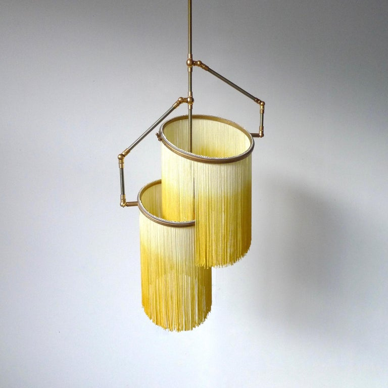 Yellow Charme Pendant Lamp, Sander Bottinga.  Dimensions: H 65 (can be customized) x W 38 x D 25 cm. Hand-sculpted in brass, leather, wood and dip dyed colored Fringes in viscose. The movable arms makes it possible to move the circles with