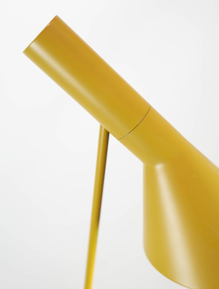 Yellow floor lamp designed by Arne Jacobsen and manufactured by Louis Poulsen. The lamp was originally designed for the SAS Royal Hotel in Copenhagen in 1957 for the hotel's design concept. The lamp here is the original made of steel with a tiltable