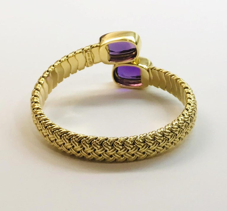 One 18K yellow gold basket-weave crossover cuff bracelet having a bezel-set rectangular/cushion -shaped cabochon-cut amethyst at each end. The gold bracelet measures approximately 10 mm wide and 4.5 mm thick. The matching pair of amethysts measure