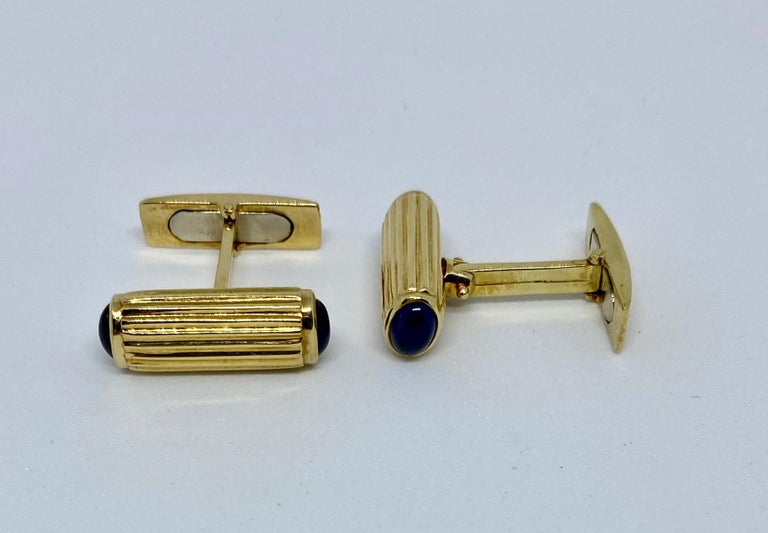 Very stylish, classic baton-style cufflinks featuring four cabochon-cut oval blue sapphires set in ribbed 18K gold.  The batons measure 20.6mm long and 7.6mm high. Each of the four oval sapphires measures 5.8mm by 4.3mm. The batons are connected to