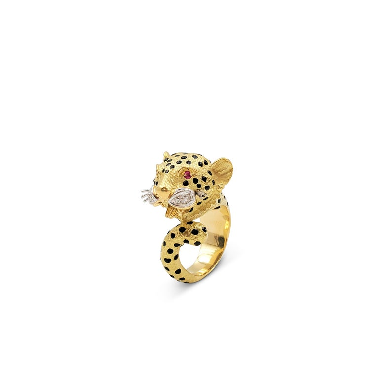 A whimsical roaring leopards head ring crafted in textured 18 karat yellow gold. The leopard's body is decorated with black onyx spots and the eyes are set with vibrant ruby stones. The whisker pads are crafted in contrasting white gold and set with