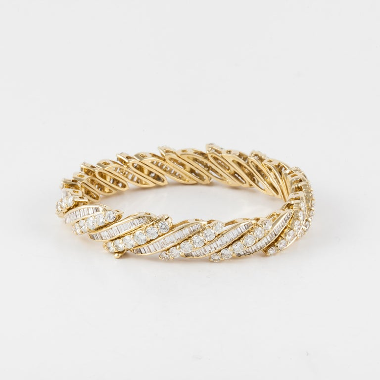 18K yellow gold bracelet with both round and baguette diamonds.  There are eighty-four (84) round diamonds totaling 9.8 carats and 196 baguette diamonds totaling 4.2 carats.  Total diamond weight is 14.0 carats; they are H-I in color and VS-SI in