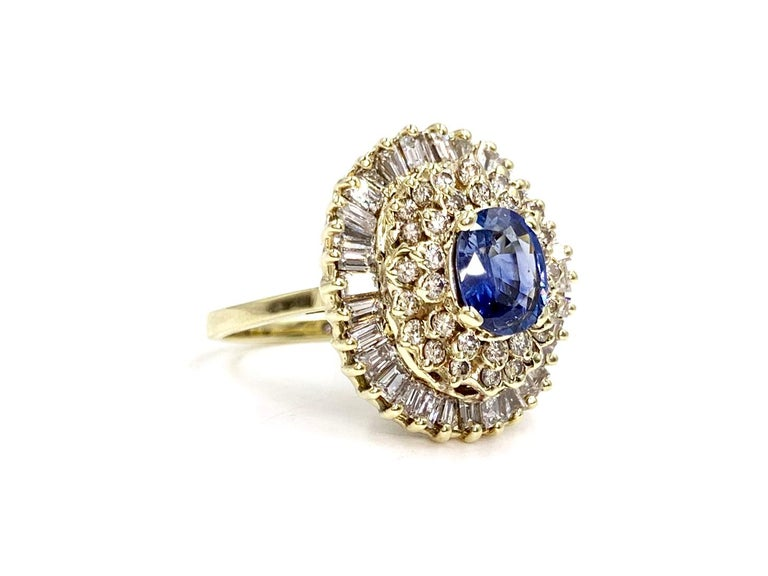 Vintage 14 karat yellow gold blue sapphire and diamond cluster style cocktail ring. Ring features a beautiful oval blue sapphire center, approximately 1 carat surrounded by approximately 1.60 carats of round brilliant diamonds and an outer halo of