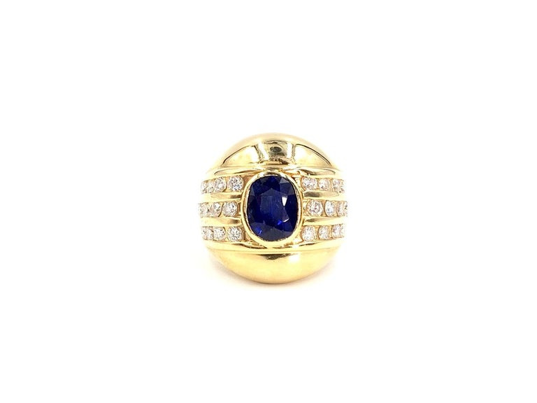 A sleek, comfortable and wearable high-polished 14 karat yellow gold wide ring with an oval bezel set blue sapphire weighing approximately 2 carats and accented with approximately .72 carats of channel set round brilliant diamonds. Oval sapphire is