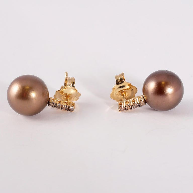These pearls run the gamut of brown colors!  The 18 karat yellow gold mountings are the perfect backdrop for the 10.00 mm Tahitian pearls and the 0.15 carats of brown diamonds.  They are secured with a standard friction back.