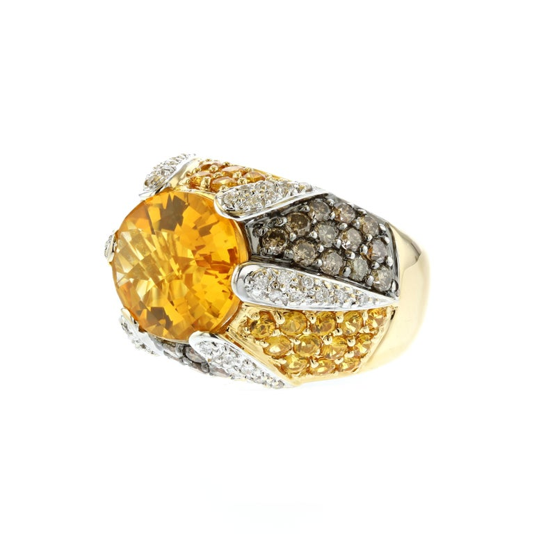 18K yellow gold ring featuring one (1) oval citrine weighing 6.70 carats.  In addition, there are twenty-nine 29 round yellow sapphires totaling 1.75 carats, twenty-nine (29) round brown diamonds totaling 1.45 carats and forty-four (44) round