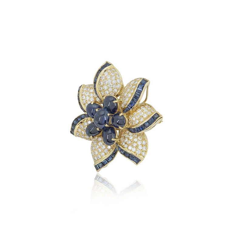 An 18k yellow gold diamond and sapphire brooch. The brooch is designed as a flower with round brilliant cut diamonds and square cut sapphires set in the petals and cabochon cut sapphires in the centre. The diamonds have a total weight of