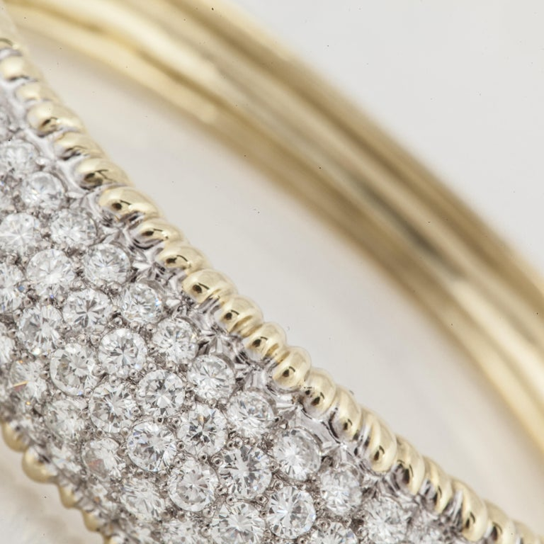 18K yellow gold diamond hinged bangle bracelet.  There are a total of 158 round diamonds totaling 10.5 carats; they are G-H in color and VS in clarity.  Measures 9/16