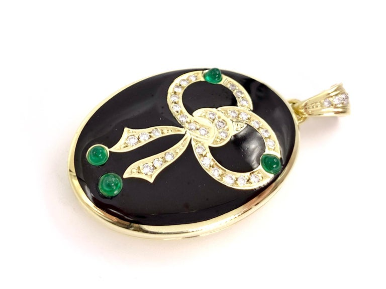 14 Karat yellow gold oval vintage bow locket featuring .40 carats of round brilliant diamonds, four vivid cabochon green emeralds and polished, smooth black enamel. Diamonds are approximately G color, VS2 clarity. Gold and diamond bale is equipped