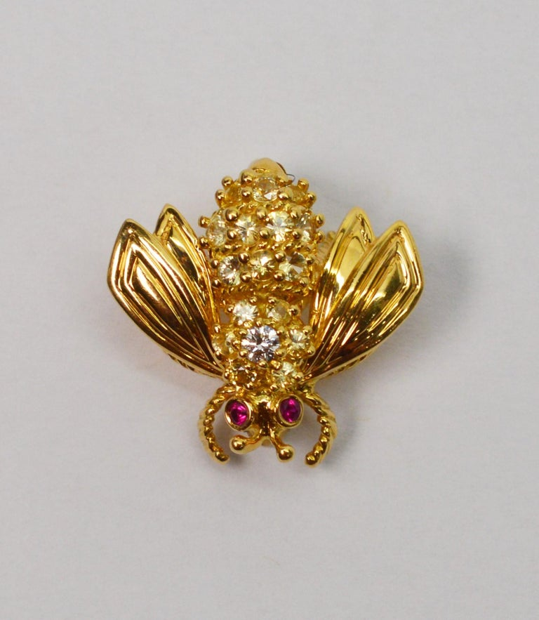 Adorable eighteen karat 18K yellow gold Tiffany & Company Bumble Bee Pin Brooch with diamond back and ruby eyes. Approximately -.75 carats. Mint condition. Measures Approximately 3/4 inch long and about the same wing to wing.