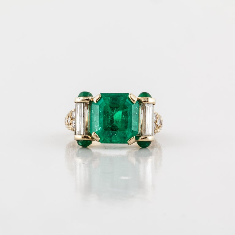 18K yellow gold Columbian emerald and diamond ring.  The center emerald is a natural Columbian emerald (AGL Report CS 28470) weighing 4.52 carats.  There are also four (4) round cabochon emeralds.  In addition, there are thirty-two (32) round