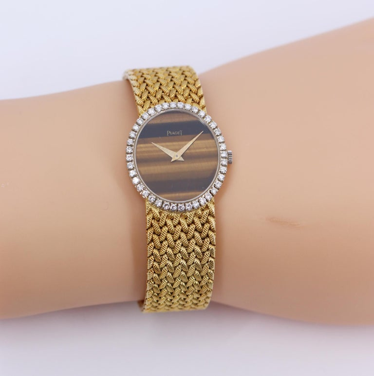 A ladies, 18K yellow gold Piaget wristwatch centered around a tiger's eye dial measuring 23mm by 20mm. Surrounding the dial are 40 round brilliant cut diamonds weighing 1ct total approximate weight, of overall F/G color and VVS2/VS1 clarity. The