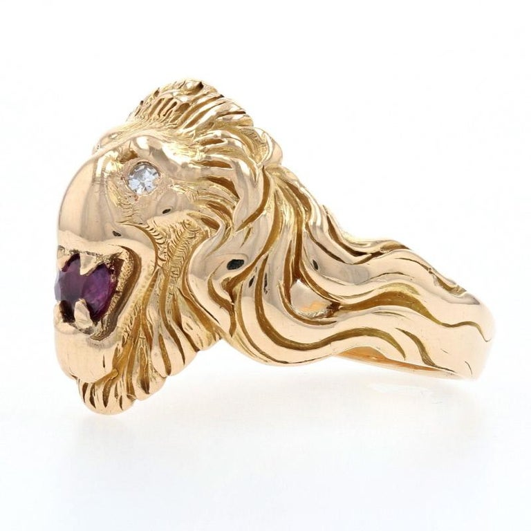 Crafted in glowing 14k yellow gold, this ring showcases a Gothic-inspired rendering of a lion's head. The lion's eyes are set with shimmering white diamonds and a ruby is displayed in its mouth.    This ring is a size 11, but it can be re-sized up 3