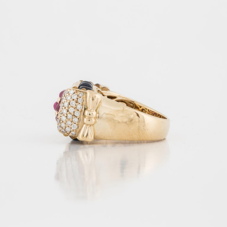 18K yellow gold ring featuring cabochon rubies and sapphires, highlighted with diamonds.  This chunky ring has ten (10) cabochon sapphires with 1.90 carats, twelve (12) cabochon rubies with 1.80 carats and sixty (60) round diamonds totaling 1.20