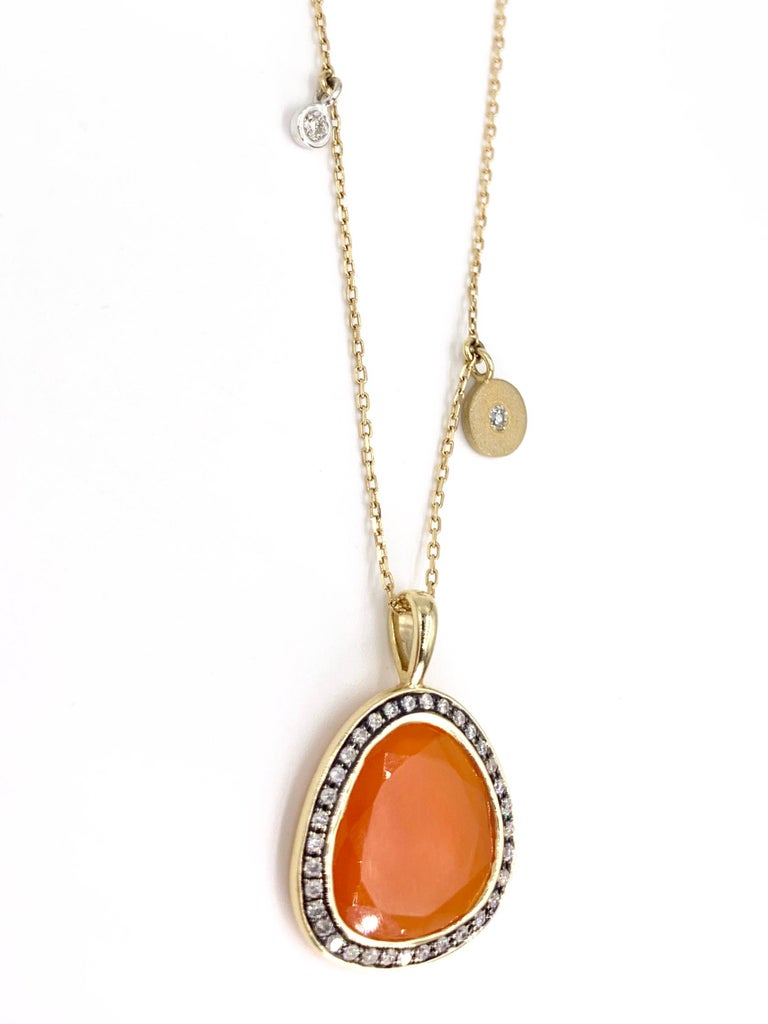 Fashionable and wearable, this 14 karat yellow gold pendant necklace features an organic shaped sliced vivid fire opal surrounded by white diamonds with two delicate accent diamonds attached to the oval link chain. White round brilliant diamonds