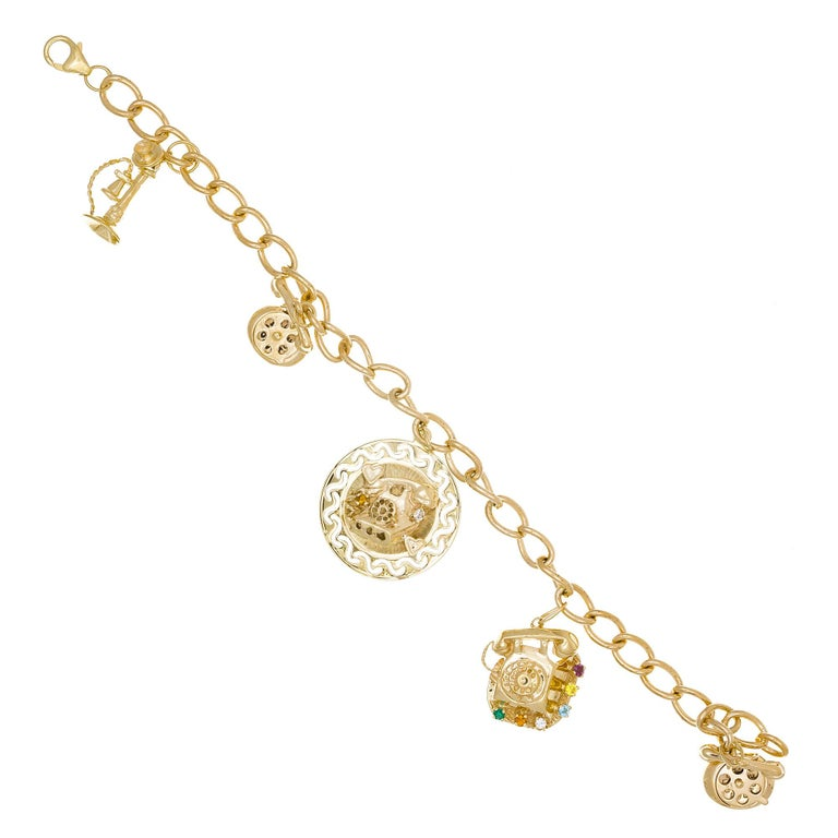 1960's solid 14k yellow gold charm theme bracelet. 5 telephone charms of different designs, styles and sizes. Two of the telephone dials rotate. 7.5 in length.    14k yellow gold  Stamped & tested 14k Length: 7.5 inches 26.2 grams 7 ¾ x 1 ¼ inch