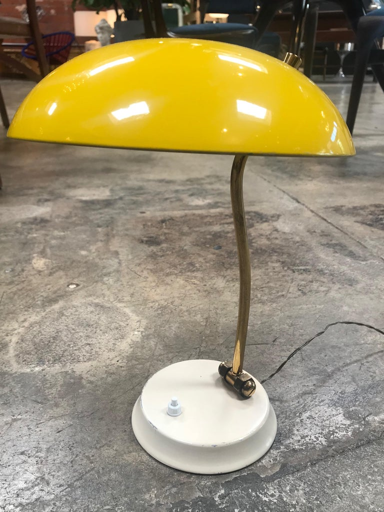 Italian vintage yellow table lamp from 1950s, the arm in brass and shade are adjustable.
