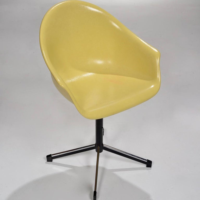 Yellow molded fiberglass swivel shell chair with arms and black metal four-legged base.  This chair is in beautiful condition and makes for a perfect desk chair.