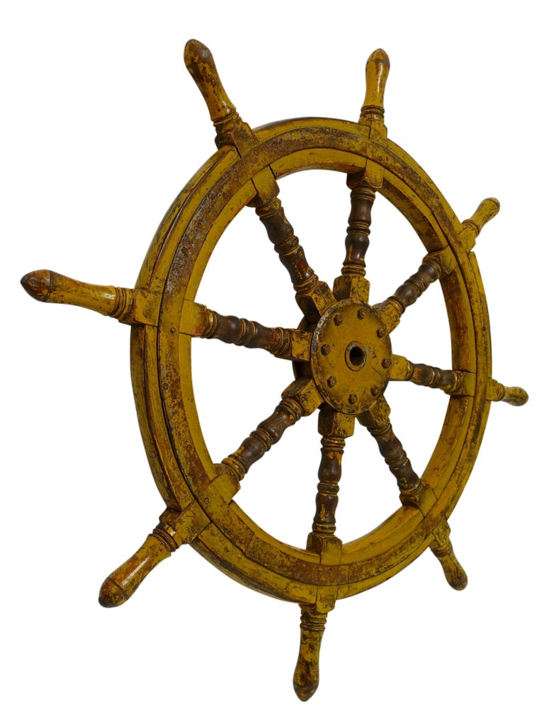 A walnut ships wheel with old yellow paint and wrought iron banding. Origin Unknown. Load of charm and character with a mix of the wood and iron and the wearing of the painted finish.