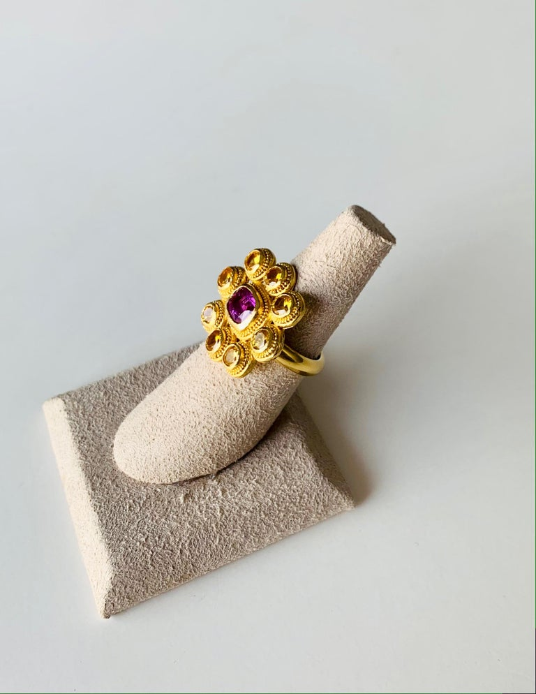 This brightly colored fancy yellow and pink Sapphire cocktail ring will add sparkle to any occasion and outfit . the stones are set in 22 Karat gold with granulation detailing . It is entirely handcrafted by the artist in her New York studio. Size