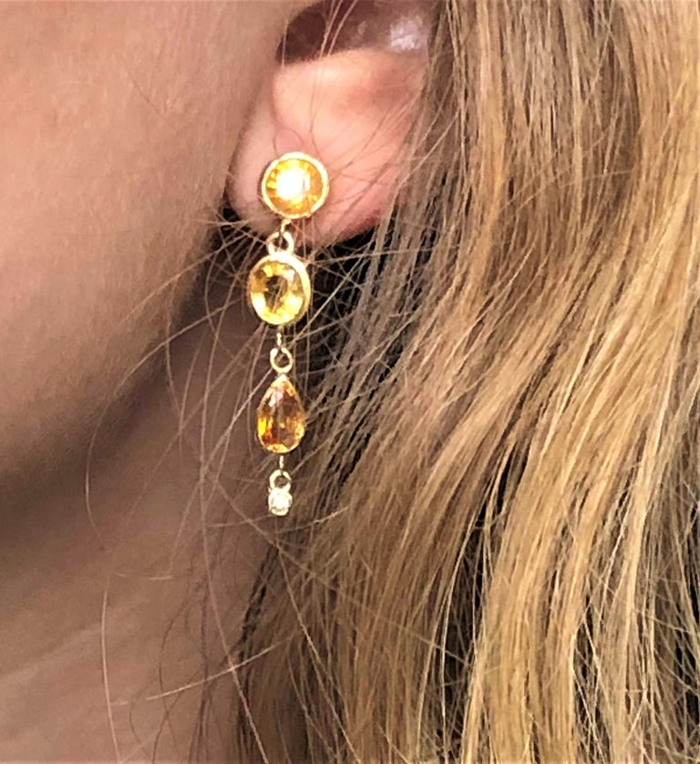 Fourteen karat yellow gold drop earrings Yellow Sapphires weighing 6.25 carat  Diamond weight 0.08 carat Country of origin Ceylon New Earrings  14 karat gold earrings are hanging off a post with push backs Our design team select gemstones for their