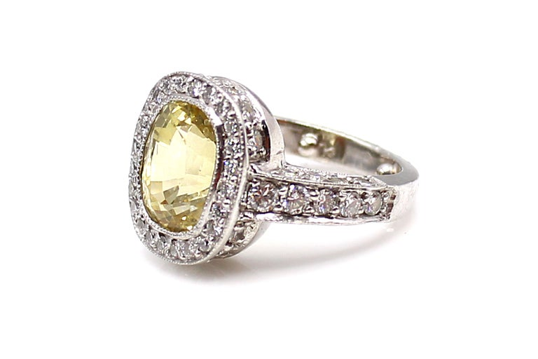 Beautifully designed and masterfully hand-crafted in platinum, this ring features an oval brilliant cut yellow sapphire. The lively and well saturated gemstone, which has been measured to weigh approximately 4.95 carats,  is bezel set and has fine