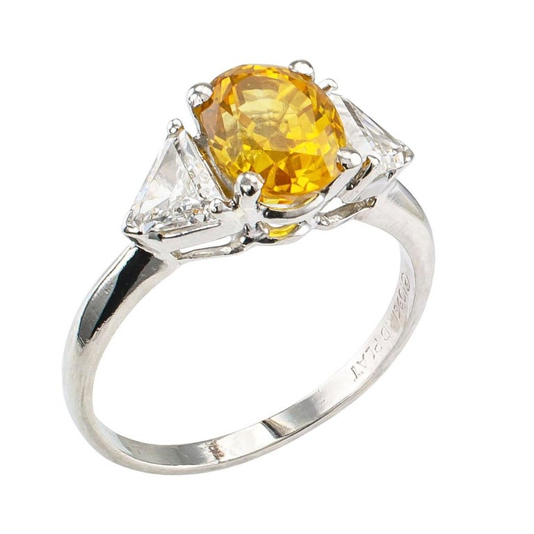 Yellow sapphire diamond and platinum three stone ring circa 1970. Centering upon an oval yellow sapphire weighing 2.06 carats between a pair of triangular diamonds totaling approximately 0.75 carat, approximately F – G color and VS clarity, mounted