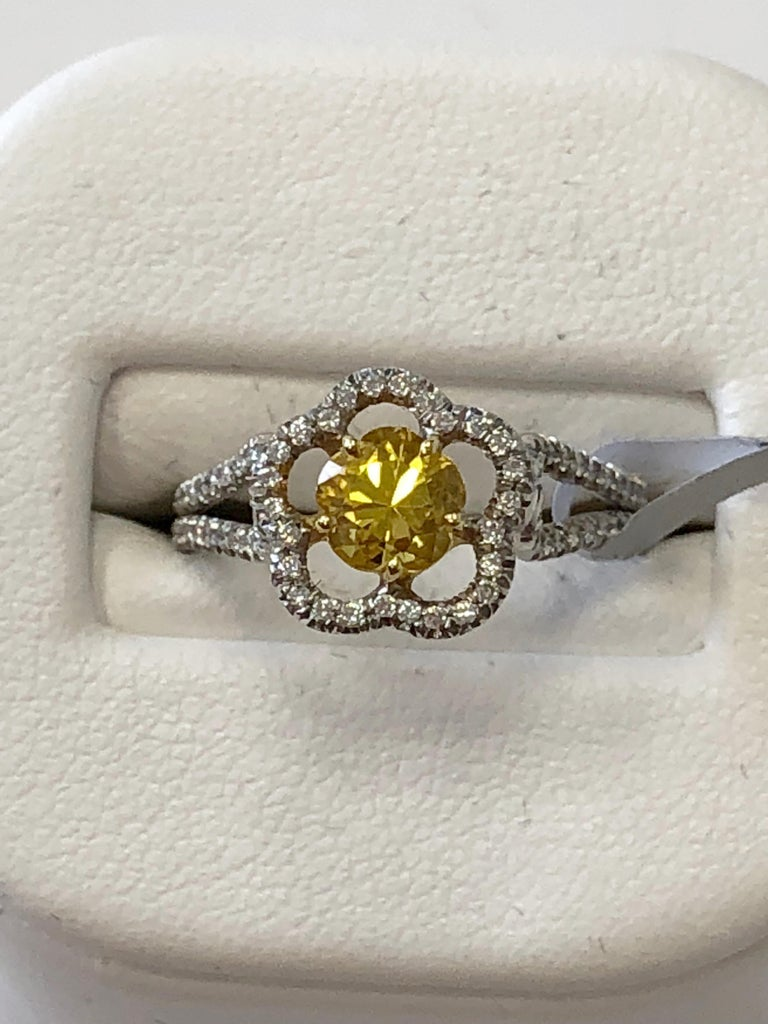 Very unique 0.88 carat flower shape yellow sapphire with beautiful bright yellow color surrounded by good quality white diamonds weighing 0.21 carats.  The ring is set in both 18k yellow and white gold with a dainty size 6 band.  Perfect for someone
