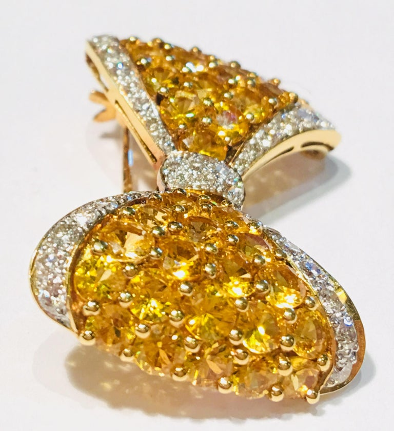 Dazzling, stylized bow tie or bow is depicted in an 18 karat yellow gold, yellow sapphire and white diamond brooch pin.  Brooch pin has great texture and contrast, featuring 40 round brilliant, prong set, vivid yellow sapphires as the body of the