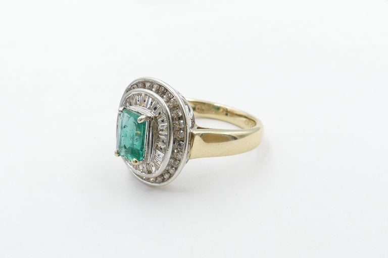 The beautiful colour Emerald centering this Ring is close to 1 carat, bluish-green in Colour, medium Tone, Emerald cut, , 4 claw set. Surrounding the Stone are 26 tapered Baguette Cut Diamonds, Colour H/J, Clarity SI1-SI2 with a further 28 Round