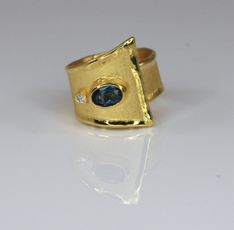Presenting Yianni Creations artisan ring crafted in Greece from 18 Karat Yellow Gold. Shiny liquid edges contrast with the brushed texture of the surface. This geometrical ring features 1.60 Carat oval cut London Blue Topaz accompanied by 0.03 Carat