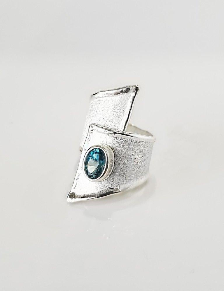 Yianni Creations presents Ammos Collection handmade artisan ring from fine silver 950 purity plated with palladium. This wide asymmetrical ring features 1.60 Carat London Blue Topaz on mat brushed texture and shiny nature-inspired liquid edges. The