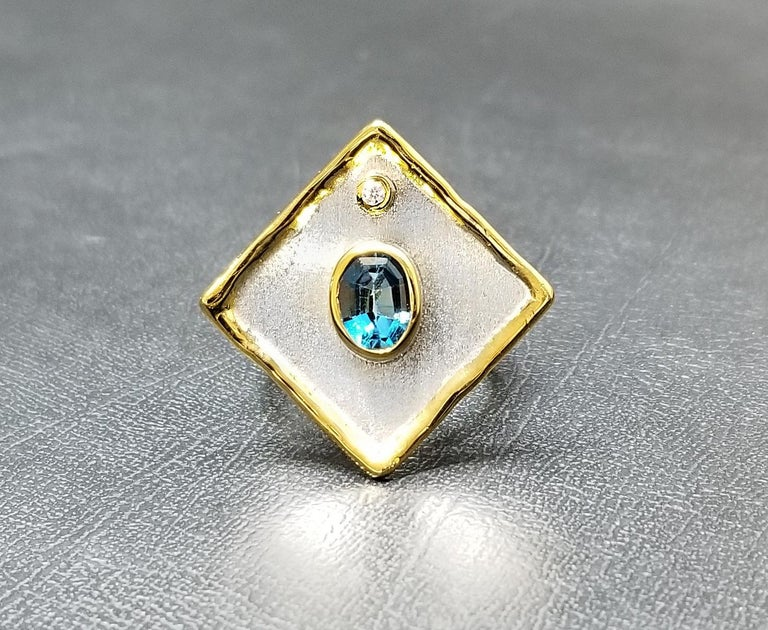 Presenting Yianni Creations - Ammos Collection fully handcrafted ring from Fine Silver plated with Palladium to resist the elements. This geometric-shaped ring features 1.60 Carat London Blue Topaz accompanied by 0.03 Carat Brilliant Cut White