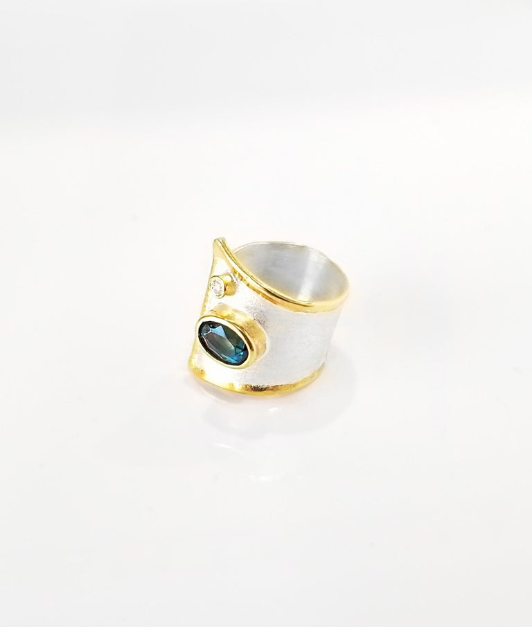 Yianni Creations Midas Collection 100% Handmade Artisan Gorgeous Ring from Fine Silver with an overlay of 24 Karat Yellow Gold features 1.60 Carat London Blue Topaz accompanied by 0.03 Carat Diamond complemented by unique techniques of craftsmanship