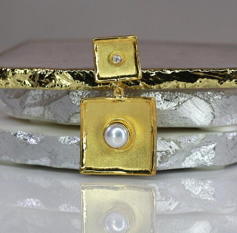 This is Yianni Creations handmade artisan slide crafted in Greece from 18 Karat Yellow Gold. This gorgeous square-shaped dangle pendant features a 7.0 MM freshwater pearl and a 0.05 Carat brilliant cut Diamond. The stunning unique look is created by