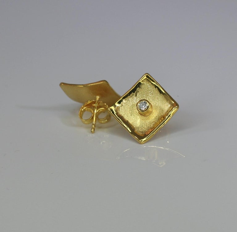 Yianni Creations Stud Earrings in diamond shape all handmade from 18 Karat Yellow Gold in Greece in our workshop using ancient techniques of craftmanship - brushed texture and nature-inspired liquid edges. Each earring is decorated with 0.03 Carat