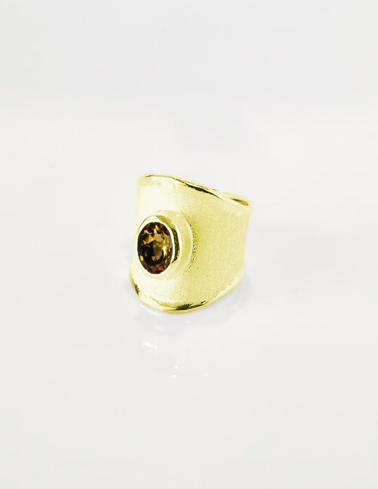 Presenting Yianni Creations ring all handcrafted in Greece from 18 Karat yellow gold. This gorgeous wide band ring features a 1.25 Carat oval cut Citrine and ancient techniques of workmanship that create a unique look. The beautiful design is also