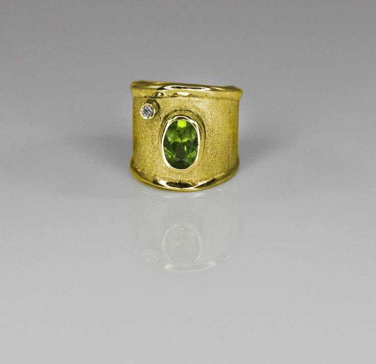 Yianni Creations presents a handmade artisan ring all crafted from 18 Karat Gold. The ring features 2.00 Carat Peridot and 0.03 Carat brilliant cut Diamond contrasting on the brushed background. The unique look is created by ancient techniques of