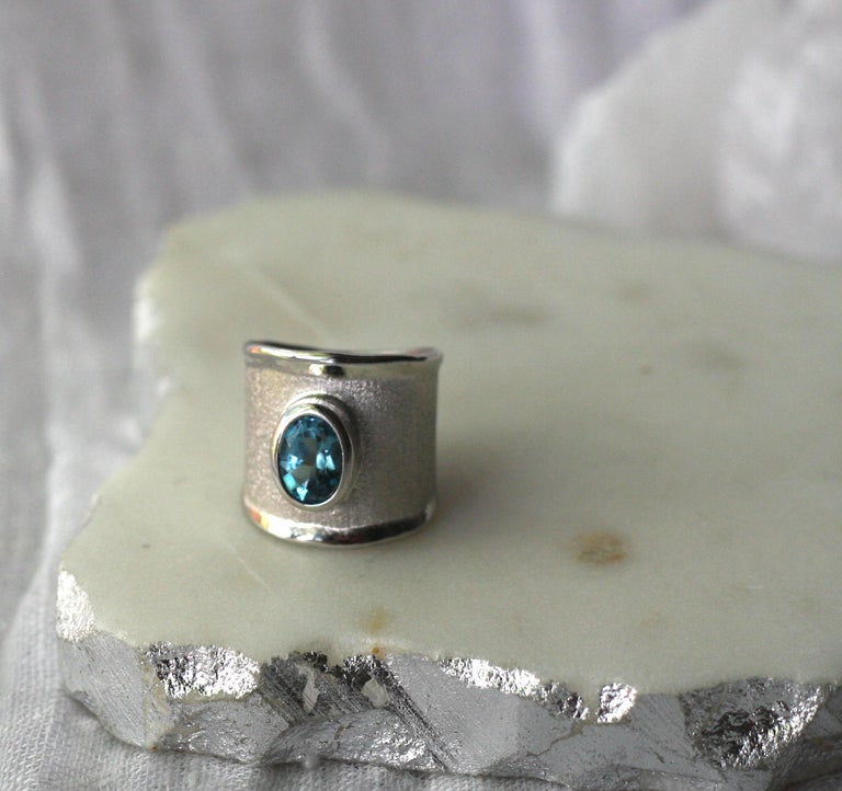This is Yianni Creations ring from Ammos Collection 100% handmade from fine silver and plated with palladium to resist tarnish. This ring is featuring 2.50 Carat London Blue Topaz complemented by unique techniques of craftsmanship - brushed texture