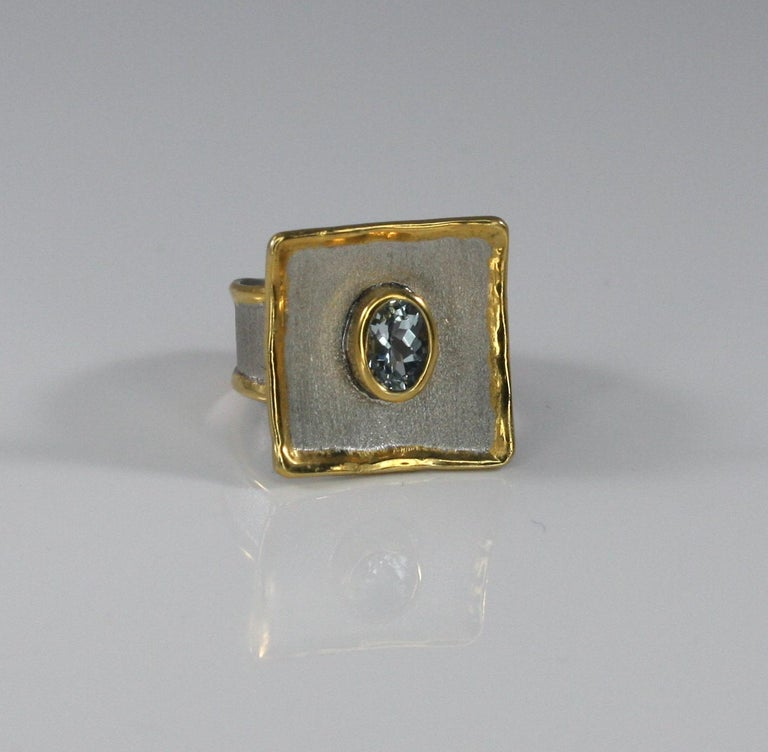 Yianni Creations handmade artisan ring is made from fine silver 950 purity plated with palladium to resist the elements. This square ring from Midas Collection has edges decorated with 24 Karat gold thick overlay and features 1.10 Carat Oval