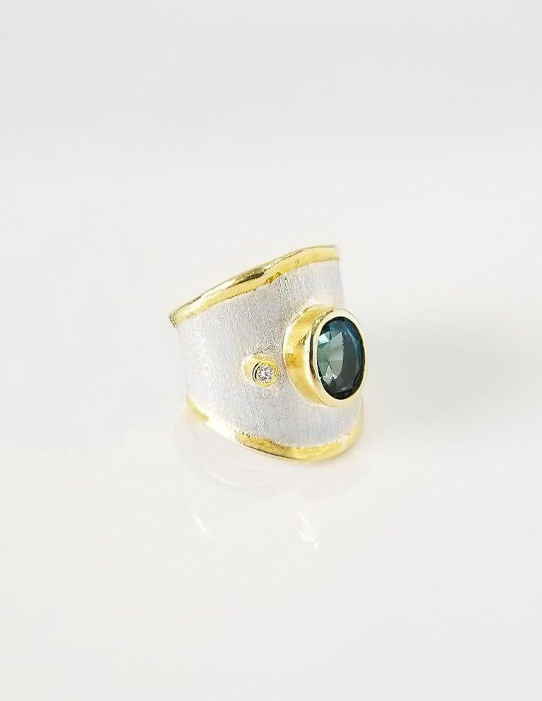 Yianni Creations Midas Collection 100% Handmade Artisan Ring from Fine Silver with an overlay of 24 Karat Yellow Gold features a 1.60 Carat Oval Cut London Blue Topaz accompanied by 0.03 Carat Diamond complemented by unique techniques of